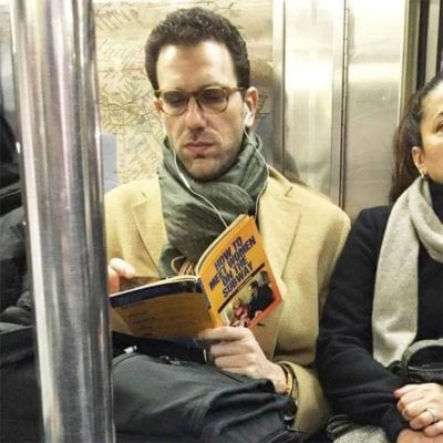 a man reading book in subway just read the name of book, weird people