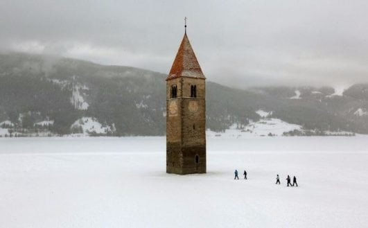 Church steeple peeking out of a frozen lake, Reschen, Italy