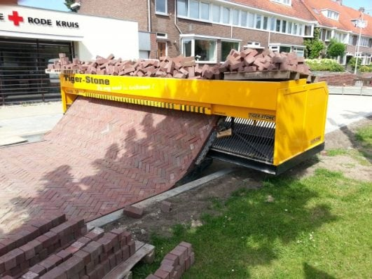 A paving machine making brick roads