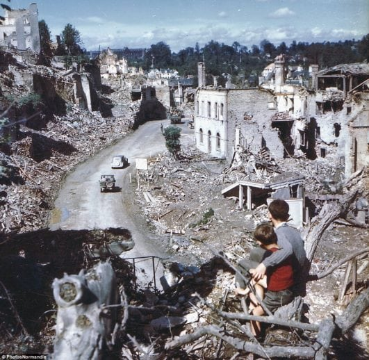 In the aftermath of the D-Day invasion, two boys watch from a hilltop as American soldiers drive through the town of St. Lo. France, 1944.